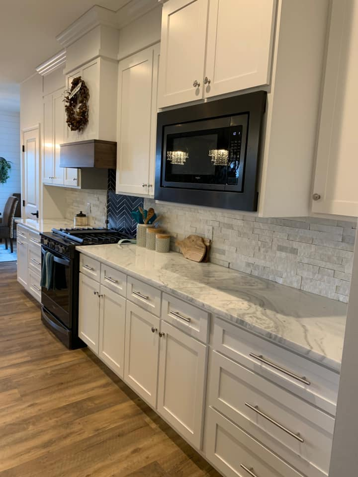 View of mont blanc marble kitchen with unique herringbone pattern tile backsplash behind the oven.